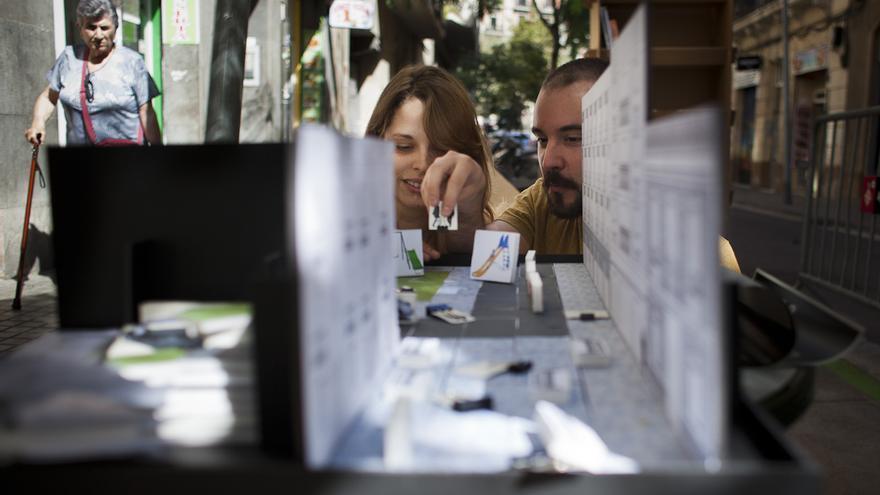 La iniciativa Park(ing) Day, en el Poble Sec de Barcelona. Dos jóvenes distribuyen figuras de mobiliario urbano sobre la maqueta. /ENRIC CATALÀ