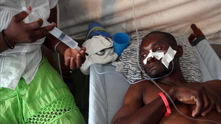 Una mujer hidrata a su esposo enfermo de cólera en un centro de Médicos Sin Fronteras en Puerto Príncipe (Haití).