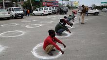 Oficiales de policía de Jammu y Cachemira obligan a las personas a agacharse dentro de un círculo marcado para mantener una distancia social este 25 de marzo