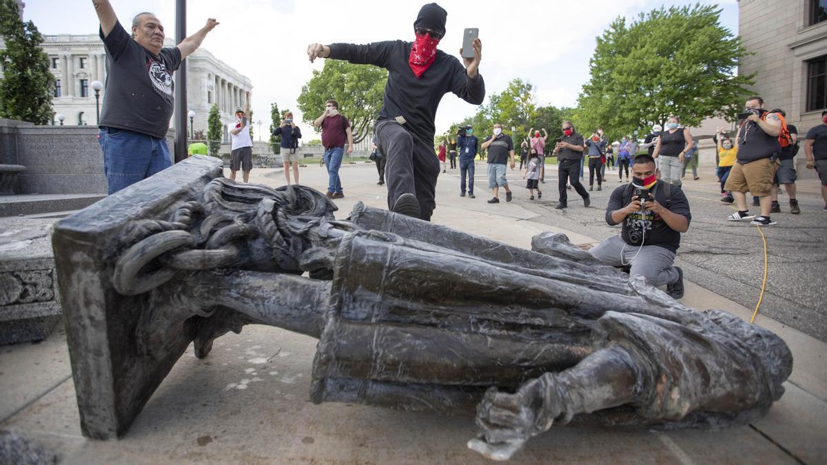 Un hombre da una patada a la estatua de Colón tras ser derribada por activistas nativos americanos en el Capitolio de Minnesota, junio de 2020.