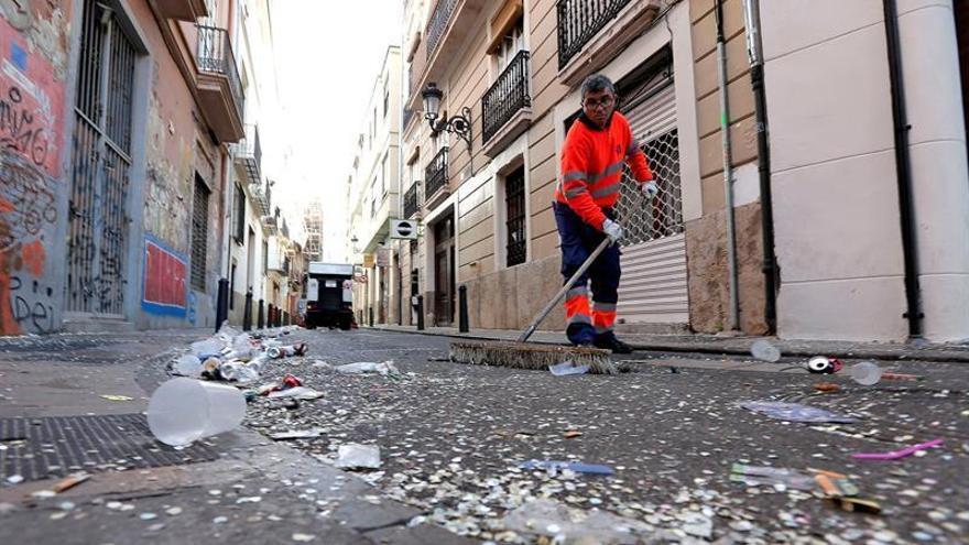 Un barrendero recoge los restos que han quedado en la calle tras una noche de fallas