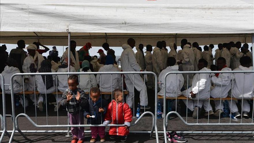 Un grupo de personas descansa bajo una carpa de la Cruz Roja después de desembarcar en el puerto de Salerno, Italia.