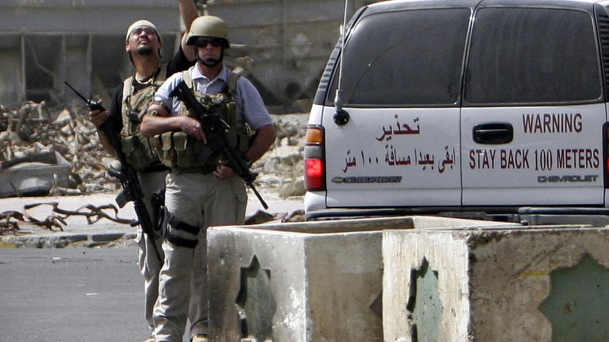 Trabajadores militares privados supervisan el lugar de un ataque bomba en Bagdad (Irak), en julio de 2005