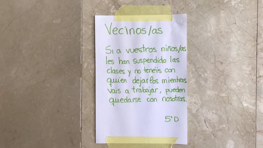 Un cartel en el ascensor de un edificio para ayudar a familias que no puedan cuidar a sus hijos en casa ante el cierre de colegios.