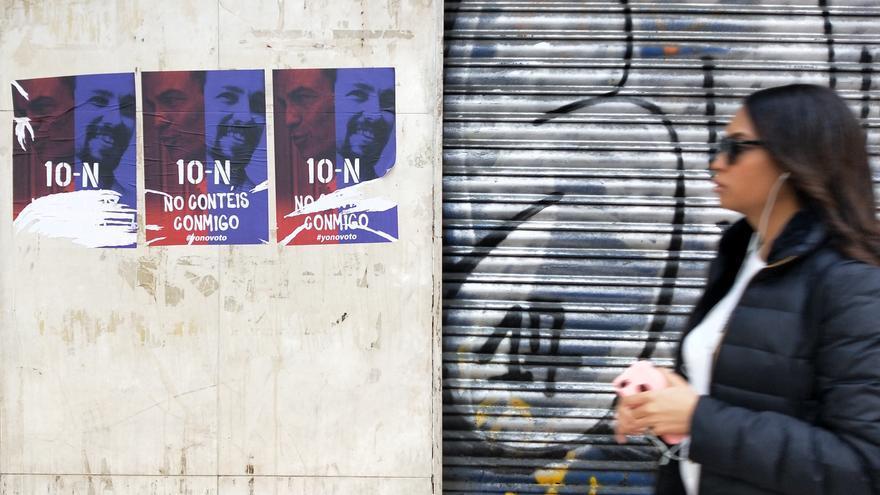 """Una mujer camina delante de los carteles con la inscripción """"No contéis conmigo"""", en Usera."""