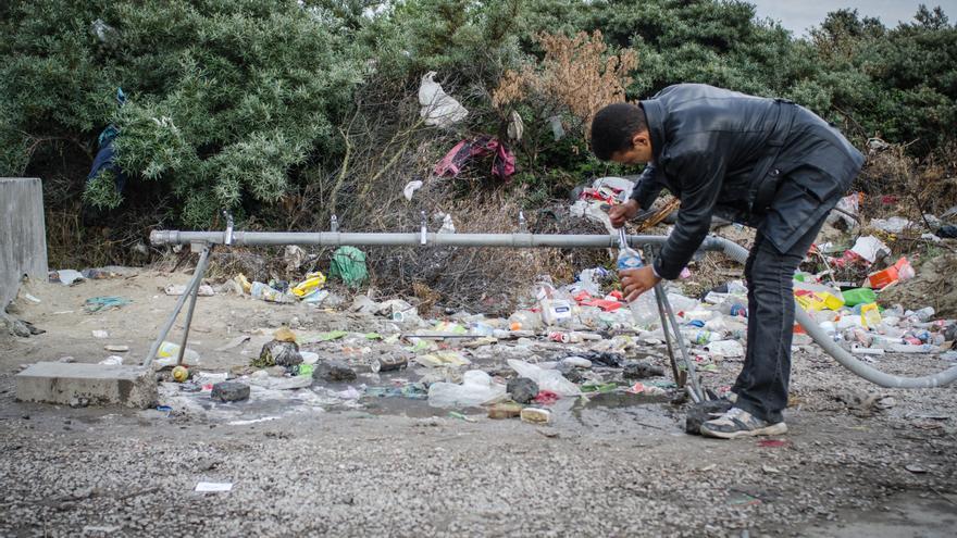 Un hombre llena una botella de agua de uno de los cinco puntos de suministro del campamento de La Jungla, en Calais. / Foto: Thom Davies.