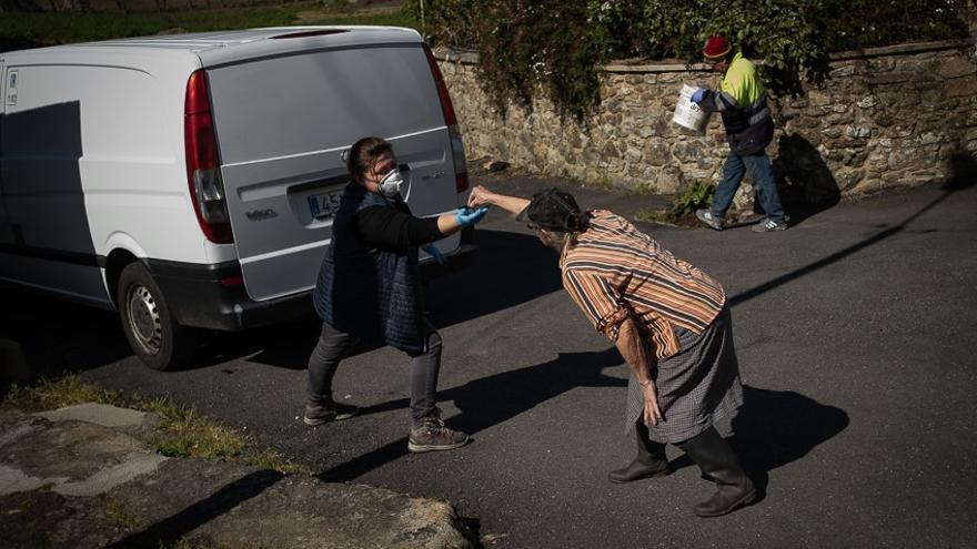 Carmen, una vecina de la aldea de Vilacoba le paga a la pescadera manteniendo la distancia de seguridad en Lousame (A Coruña).