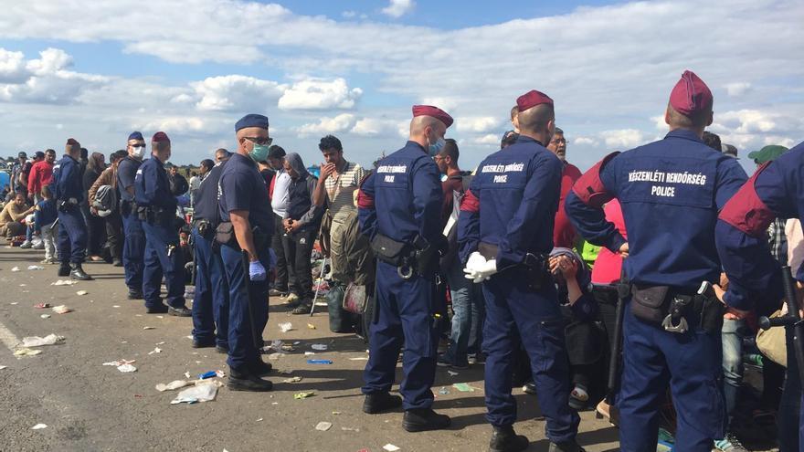 Refugiados sirios custodiados por la policía a su llegada a Hungría. Su huída es causa de la guerra y las políticas que se practican en Oriente Medio / Olga Rodríguez