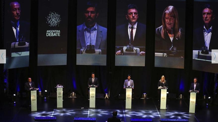 Los cinco candidatos que pariciparon en el debate y un atril vacío para el representante del oficialismo que decidió no asistir.