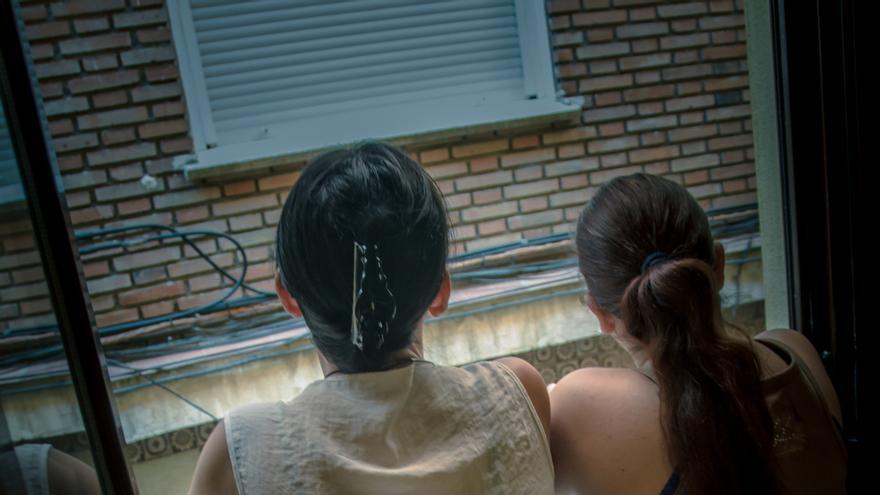 Dos personas en el edificio dignidad de la PAH contemplan la calle desde el balcón de su casa de realojo