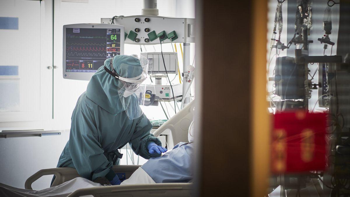 Un trabajador sanitario atiende a un paciente en una camilla de una UCI