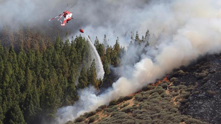 Un helicóptero en el incendio declarado este sábado en la zona de Artenara en el oeste de la isla de Gran Canaria. EFE/Elvira Urquijo A.