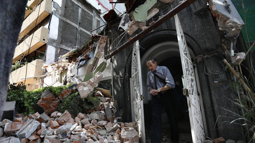 Un hombre camina hacia fuera de la puerta un edificio derrumbado tras el terremoto, en el barrio mexicano de la Condesa, en Ciudad de México.