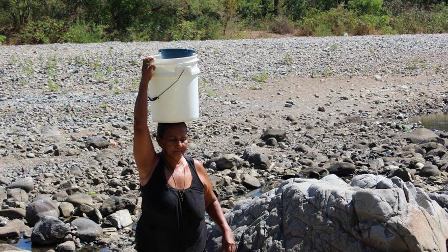 Una mujer transporta agua en su cabeza en una de las comunidades nicaragüenses.