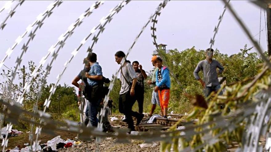 Migrantes son detenidos por una barricada en una vía férrea que conecta la frontera de Hungría con Serbia ayer, martes 15 de septiembre de 2015, en Röszke, Hungría./ EFE.