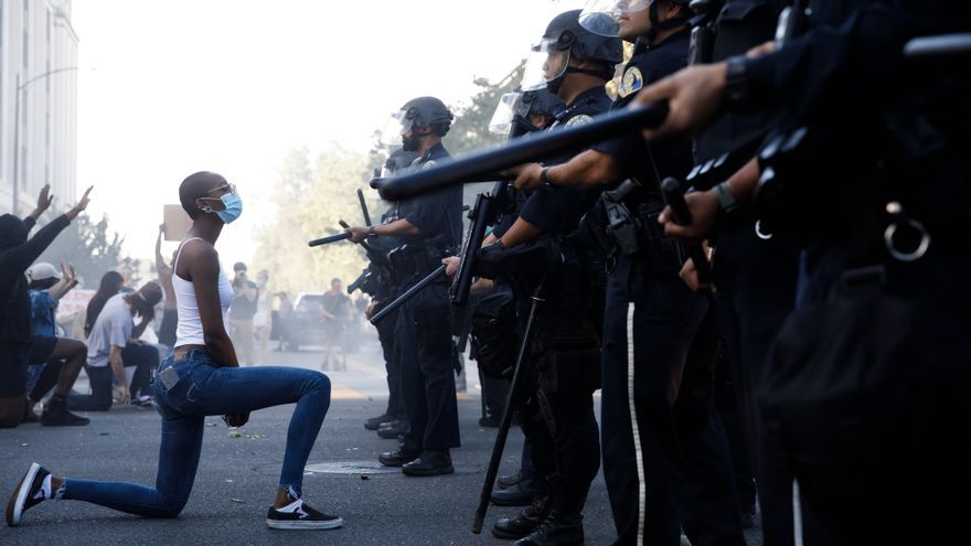 Manifestante en San José (California) arrodillada delante de la policía