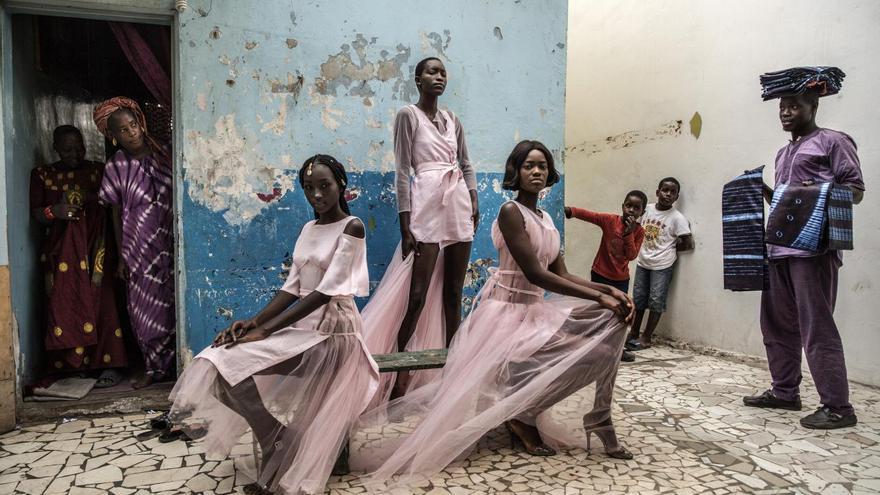 'Dakar Fashion', ganadora del primer premio en la categoría 'Retratos'. Diarra Ndiaye, Ndeye Fatou Mbaye y Mariza Sakho visten atuendos del diseñador Adama Paris, en el barrio de Medina en Dakar, la capital senegalesa, mientras los curiosos residentes observan.
