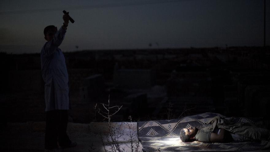 Un hombre apunta con una linterna el cuerpo muerto de otro hombre asesinado por el ejército sirio durante un bombardeo en un cementerio en Aleppo, Siria. Esta es una de las fotografías galardonadas con el premio Pulitzer (13 de octubre de 2012) / AP PHOTO. MANU BRABO