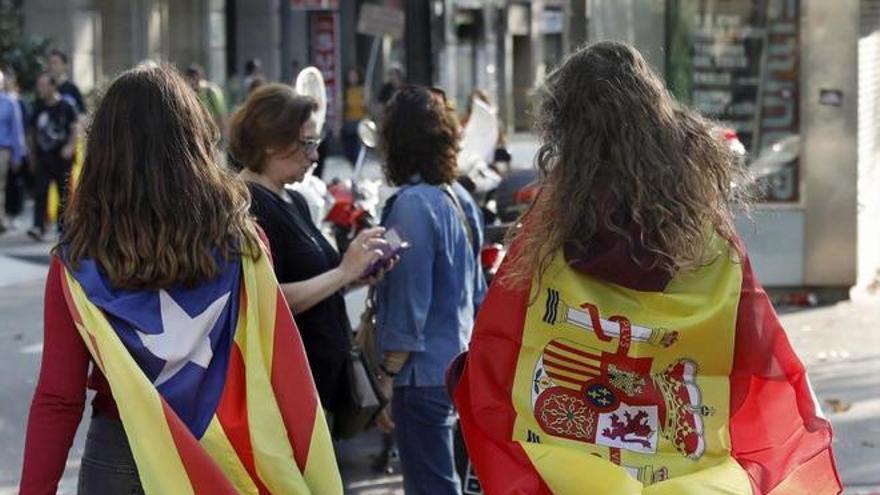 Dos amigas se dirigen a una manifestación portando una estelada independentista y una bandera de España