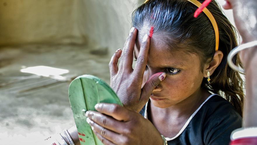 Dos mujeres ayudan a una niña casada a ponerse el 'bindi' en la frente, la marca que refleja su unión./ Zigor Aldama