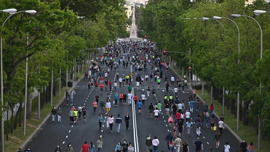 Multitud de personas pasean y hacen ejercicio por el Paseo de la Castellana, en Madrid.