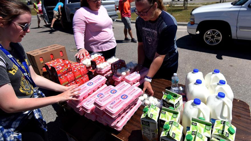 Voluntarias del banco de alimentos Second Harvest de Florida preparan paquetes de huevos, leche y zumos este 3 de abril