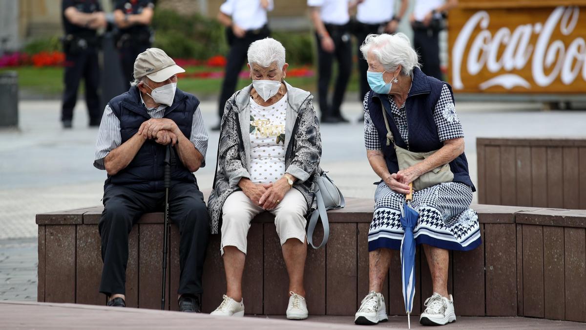 Unos ancianos conversan protegidos con mascarillas este viernes en San Sebastián. EFE/Juan Herrero.