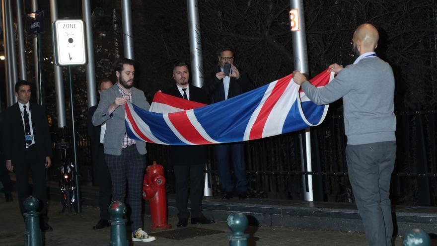 Funcionarios de la Unión Europea doblan la bandera de Reino Unido tras arriarla de la sede del Europarlamento