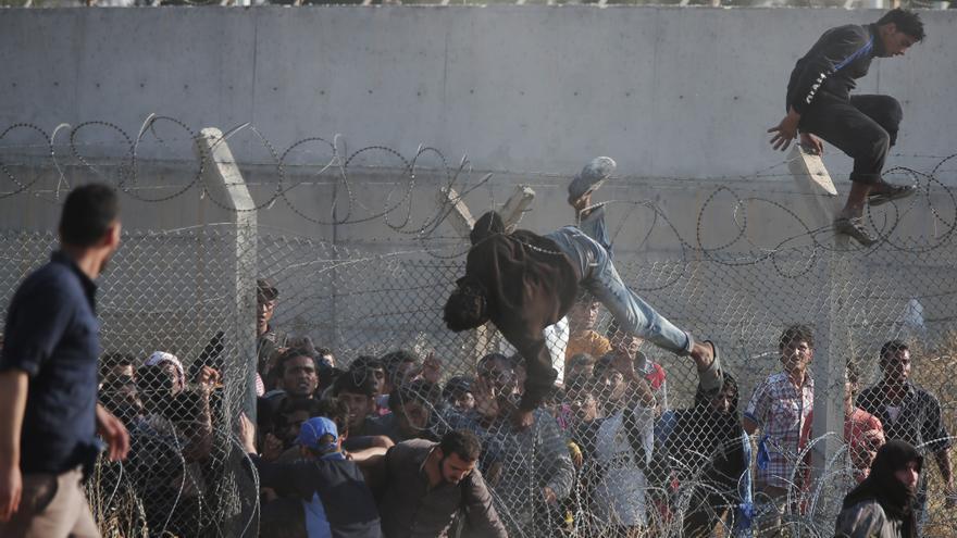 Refugiados sirios cruzan la valla fronteriza que separa su país de Turquía tras romper la alambrada, en la zona de Akcakale. La multitud huye de los enfrentamientos armados en el norte de Siria entre kurdos y los islamistas del autoproclamado Estado Islámico. / (AP Photo/Lefteris Pitarakis).