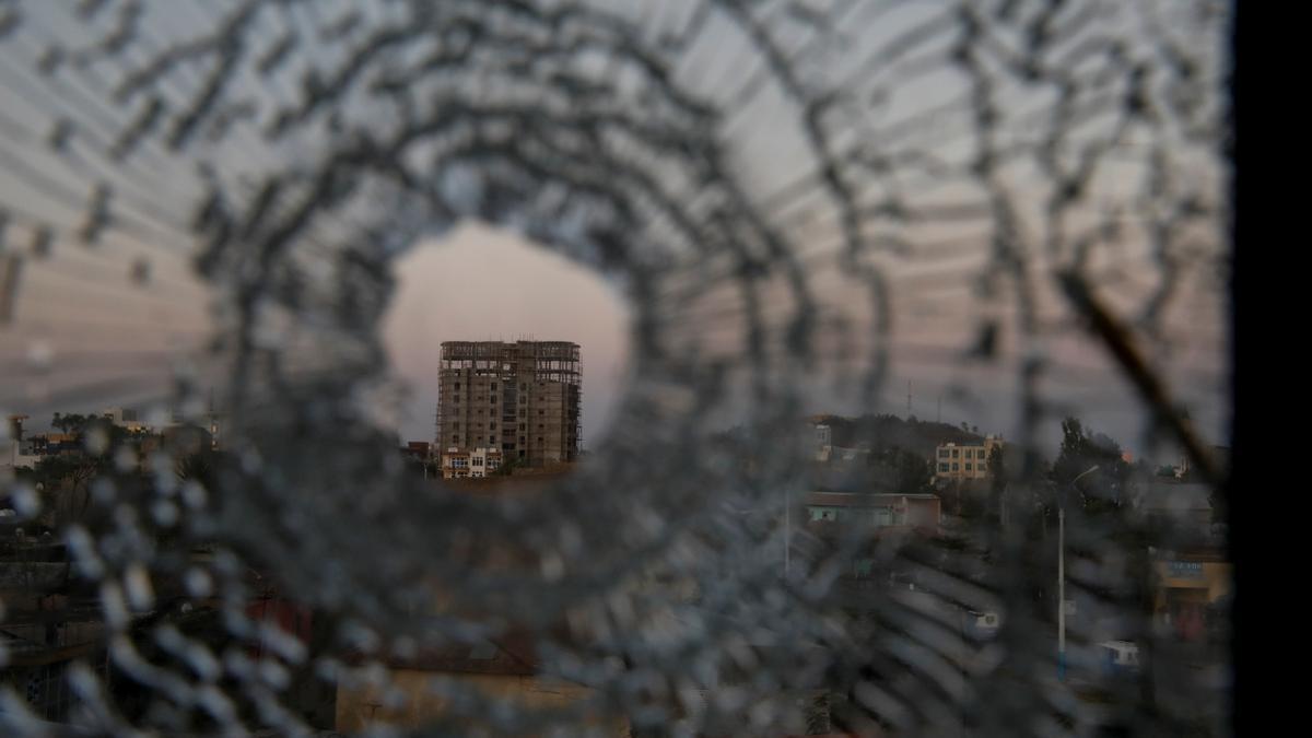 Un edificio visto a través de un agujero de bala en una de las ventanas del Hotel África de la ciudad de Shire, en Tigray