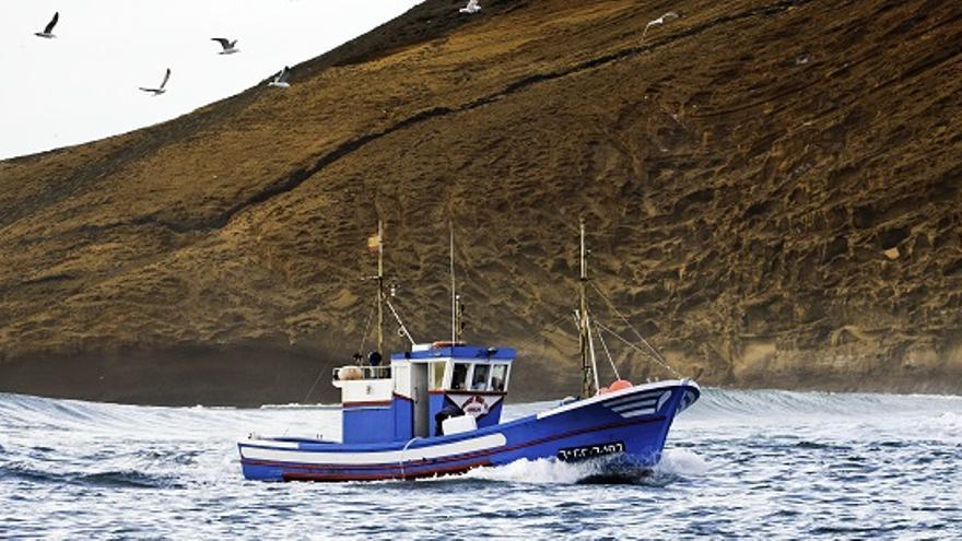 Barco pesquero con Alegranza al fondo