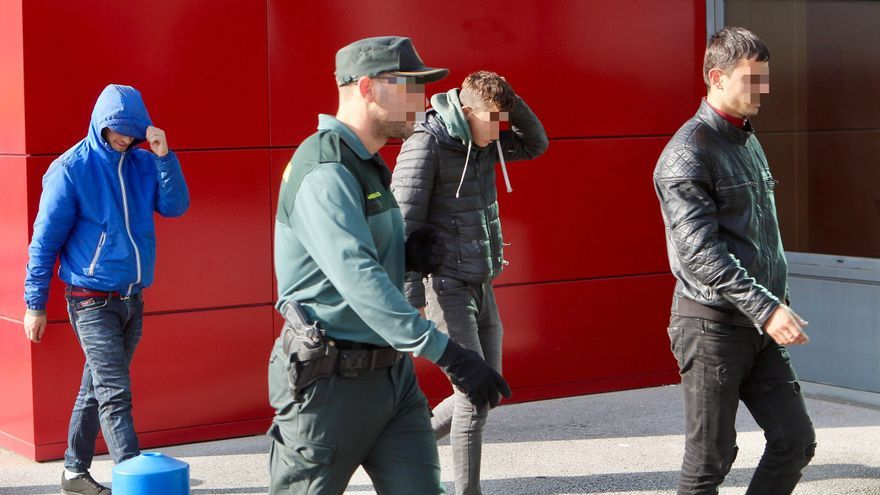 Un agente conduce a tres jóvenes polizones que intentaban acceder al ferri
