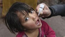 Un trabajador de los servicios sanitarios suministra la vacuna de la polio a una niña en Jalalabad (Afganistán)