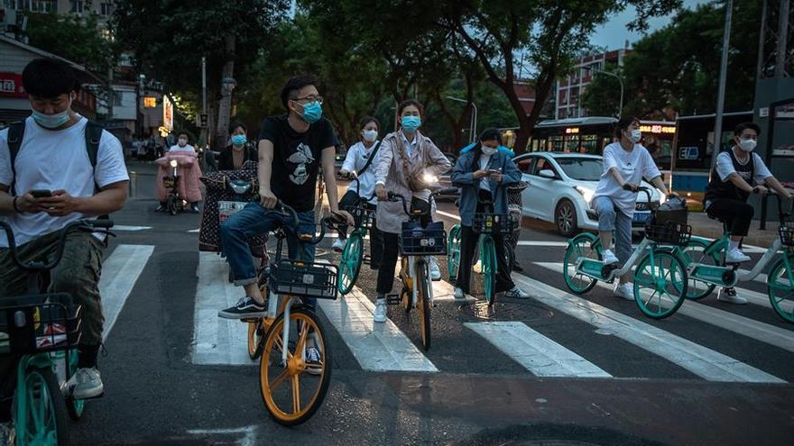 Ciudadanos chinos en bicicleta protegidos con mascarillas.