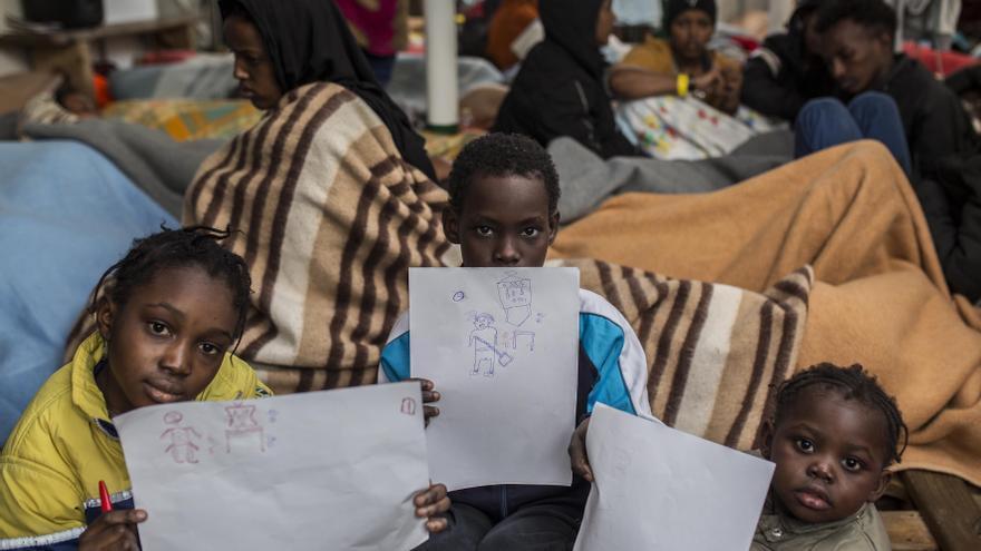 Varios de los niños rescatados muestran los dibujos que han hecho durante la tarde / Olmo Calvo