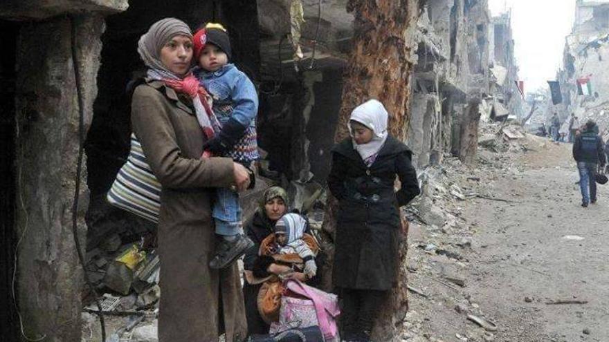 Una familia de habitantes del barrio de Yarmuk entre las ruinas. Foto: Yarmouk Media Network