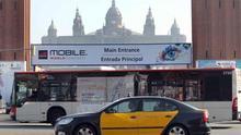 Un autobús de TMB passa davant d'un cartell del Mobile a la plaça Espanya de Barcelona