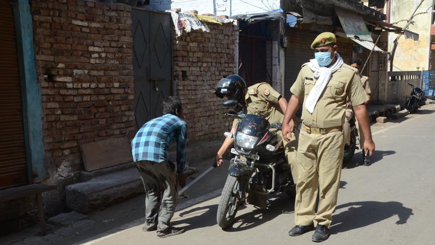Un policía golpea con un palo a un hombre por saltarse el confinamiento obligatorio impuesto en India.