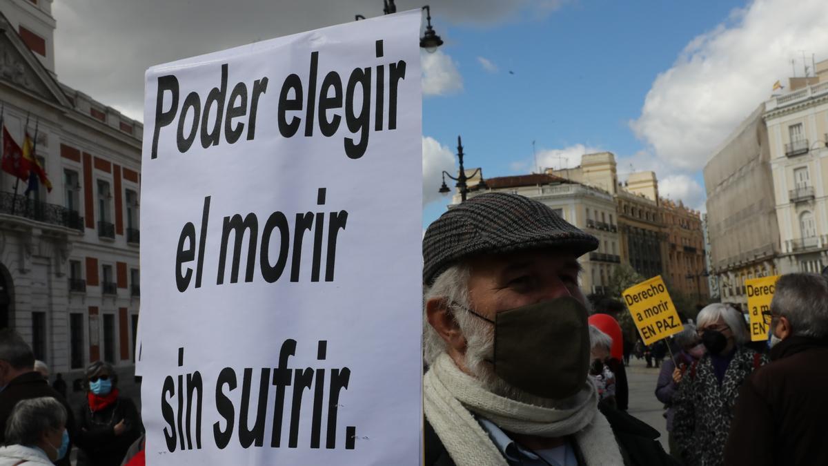 Un hombre con un cartel en el que se lee: 'Poder elegir el morir sin sufrir' durante una concentración de Derecho a Morir Dignamente en la Puerta del Sol, en Madrid