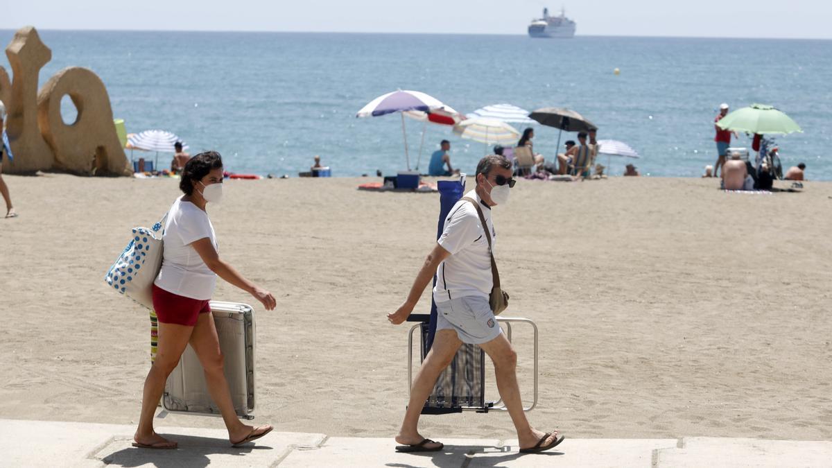 Archivo - Dos personas con mascarilla acceden a la playa