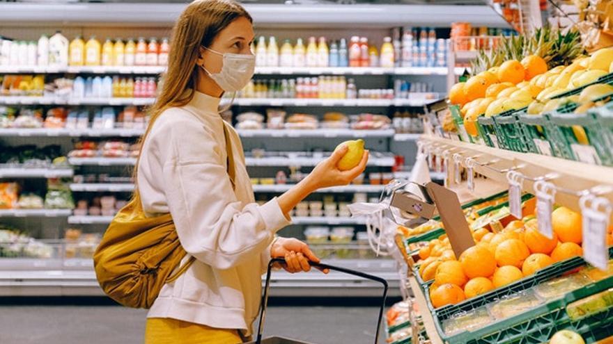 Una mujer compra fruta en un supermercado.