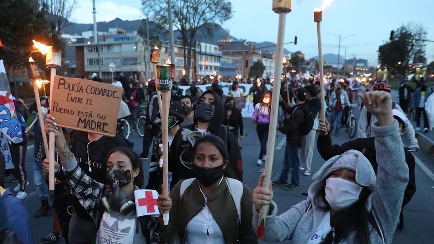 Personas sostienen antorchas este martes durante una manifestación en Bogotá (Colombia). Cientos de personas hicieron este martes una marcha y un plantón a los que asistieron estudiantes, transportadores y gente del común que reunió motivos para protestar, como la falta de ayudas del Gobierno del presidente Iván Duque durante la pandemia COVID-19, el asesinato sistemático de líderes sociales y la violación de una niña indígena embera por parte de siete soldados colombianos.