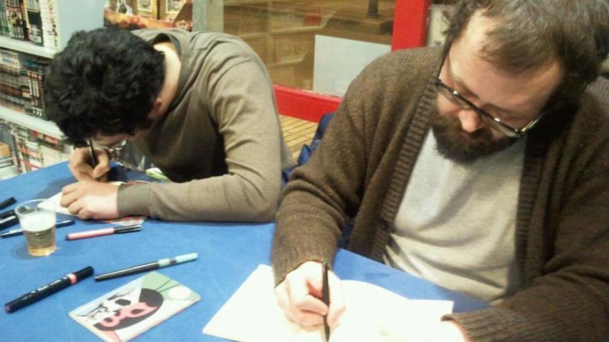 Alberto Guitián, a la derecha, dibujando