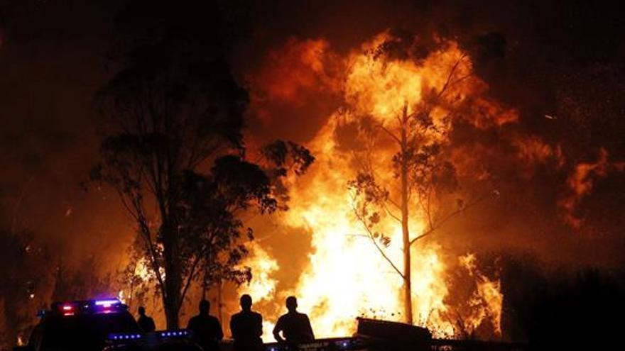 La Guardia Civil impide el acceso a la parroquia de Chandebrito donde han aparecido dos personas calcinadas en el incendio que mantiene aislada la localidad pontevedresa.