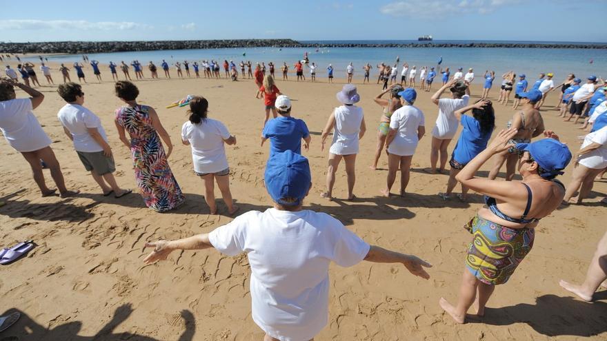 Un grupo de personas mayores participa en una de las actividades organizada por Ansina en la playa de Las Teresitas