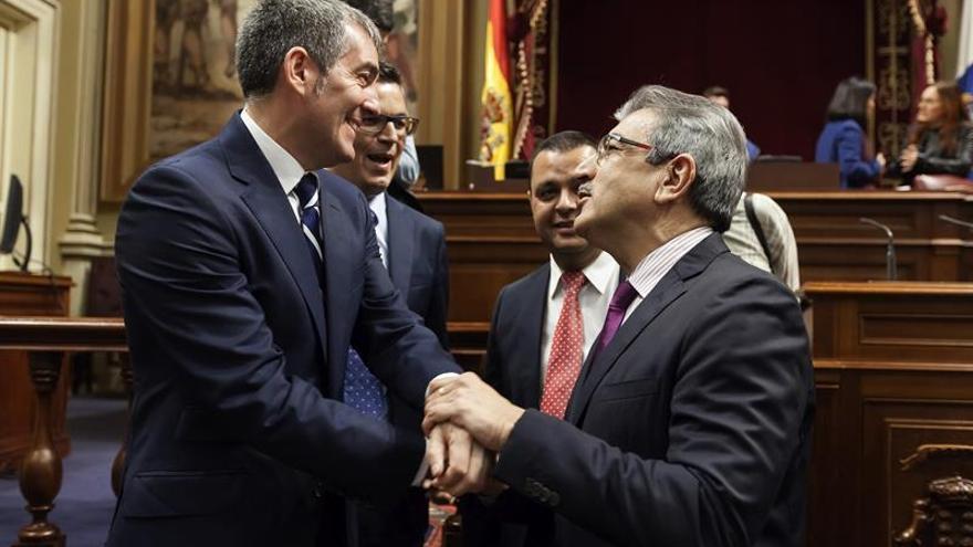 El presidente del Gobierno de Canarias, Fernando Clavijo (i), conversa con el diputado de Nueva Canarias Román Rodríguez (d), momentos antes del inicio de un pleno del Parlamento.