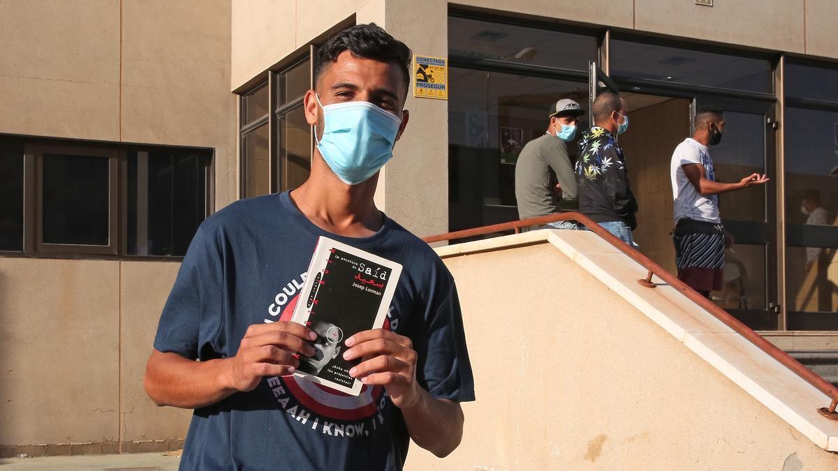 Una de las personas alojada en una nave cedida por Bankia al Ministerio de Migraciones como recurso de acogida, muestra el libro 'La aventura de Saíd'.
