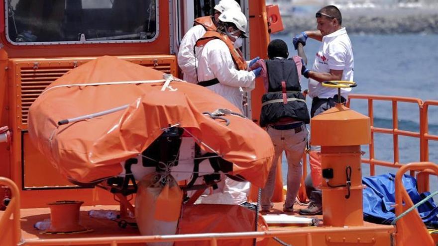 Personal de Salvamento Marítimo ayudan a uno de los 34 inmigrantes que han sido desembarcados en Arguineguín  tras ser rescatados de una patera a unos 31 kilométros al sur de Maspalomas (Gran Canaria) (EFE/ÁNGEL MEDINA G.)