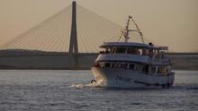Imagen del ferry cruzando el río, con el puente internacional al fondo.