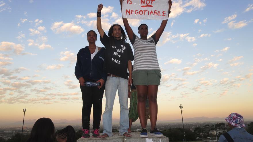 Varios estudiantes sudafricanos sobre la base donde estaba situada la estatua recién retirada/ Lalo García